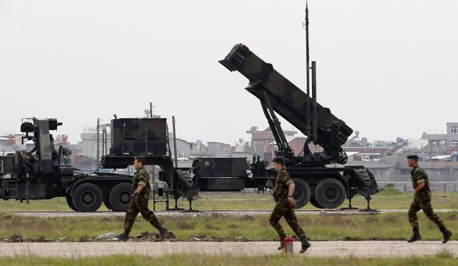 Dutch soldiers run in front of the Patriot system as they get ready for a media day at a military airbase in Adana, southern Turkey