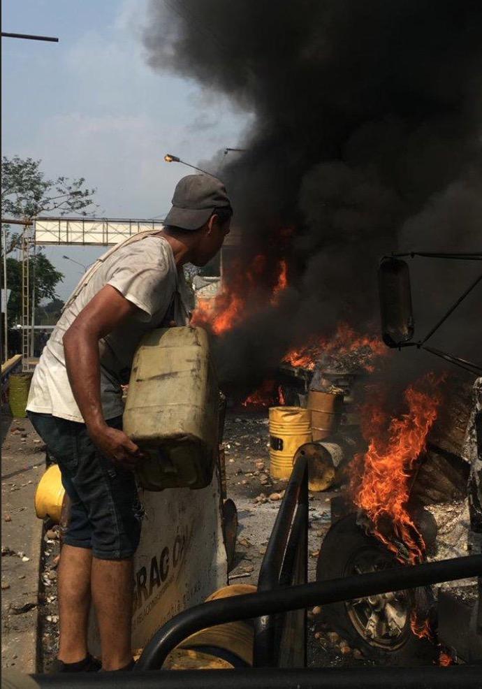 Un guarimbero, desde Colombia, apagando el fuego del camión de ayuda «humanitaria» con gasolina ;)